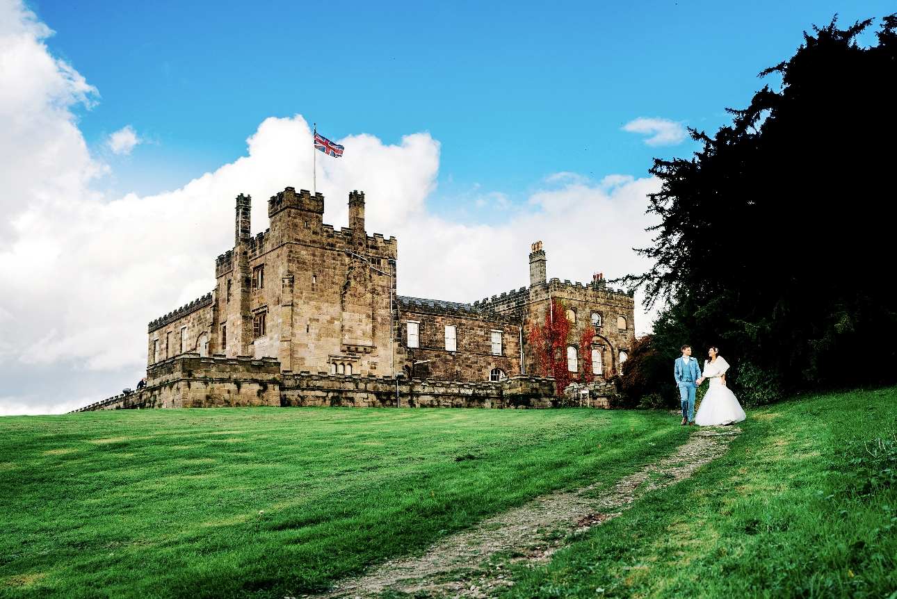 Couple walk around the grounds in front of Ripley Castle