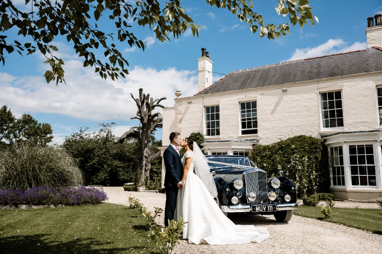 Couple in front of venue with wedding car