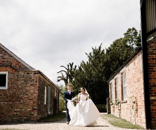 Groom hold brides dress whilst walking through grounds