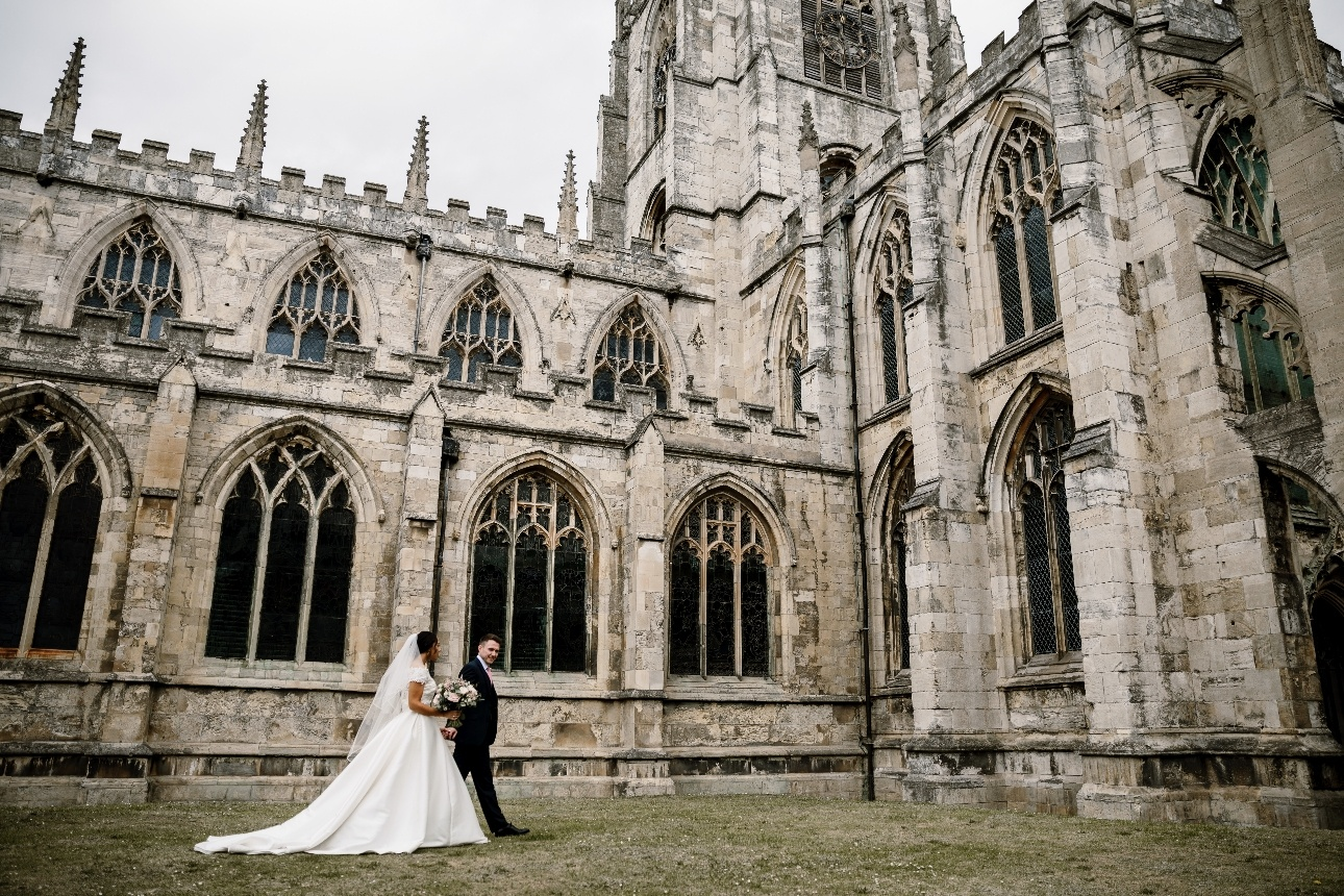 Bride and groom walk in the grounds of St Mary's Church in Beverley