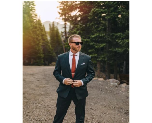 green suit on model standing in road at sunset