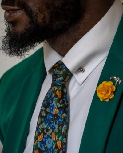 man in green suit and floral tie