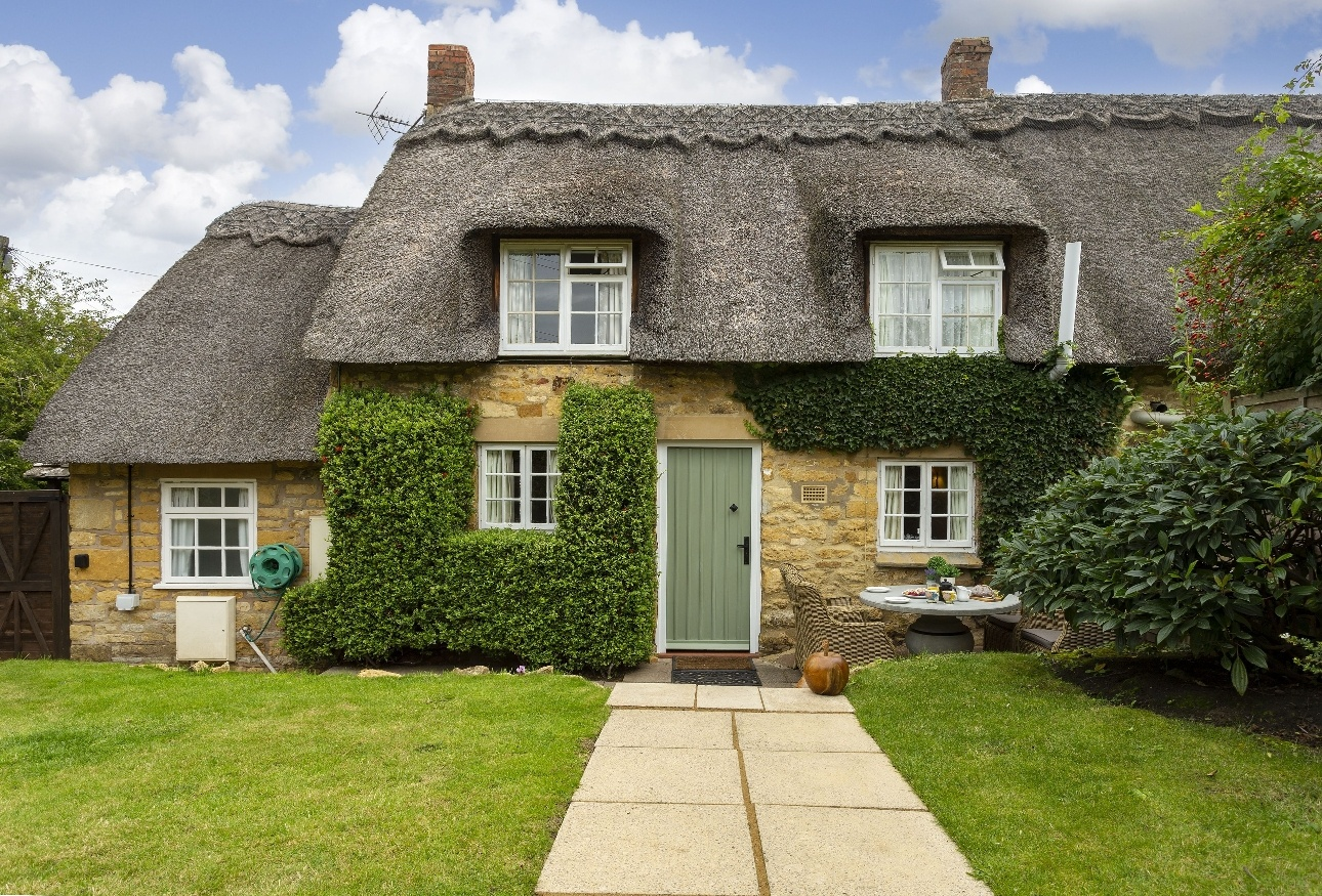 cottage with thatched roof green door