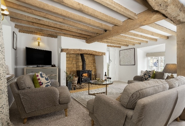 cosy lounge cream sofas woodburner beams on ceiling