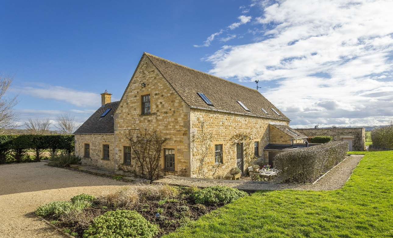 yellow stone cottage, manicured garden fields around sunny day