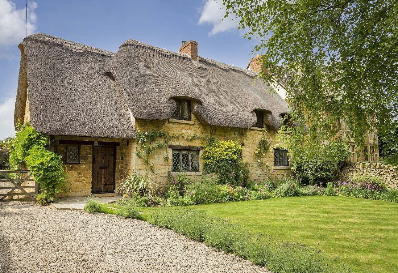 yellow stone traditional cottage with thatched roof picture-box style