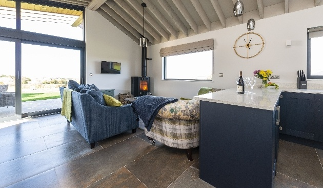 open plan living room blue sofa and log burner large windows with views