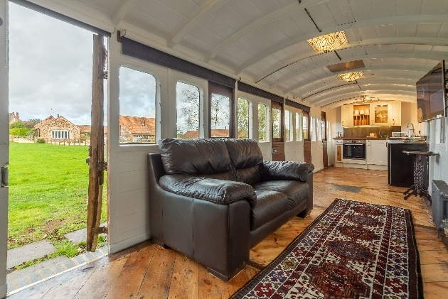 lounge area inside train leather sofa with open plan kitchen