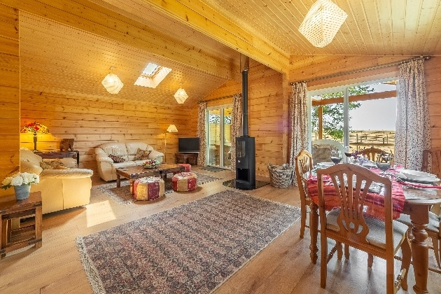 open plan lounge with table sofa and wood burner