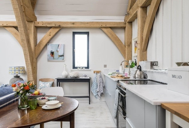 open plan kitchen with wooden ceiling beams on view