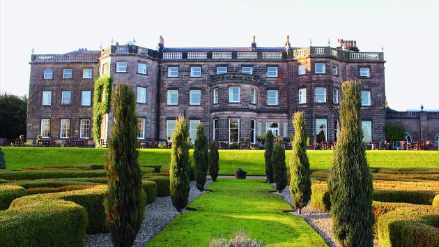 grey brick historic country manor house with manicured grounds