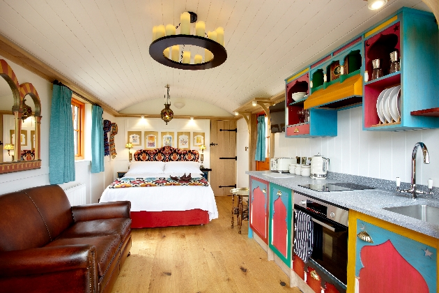 Interior of hut with leather sofa and brightly painted kitchen suite