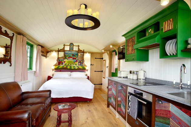 inside shepherd hut which has a leather sofa and brightly coloured folk-style kitchen cupboards and a large bed