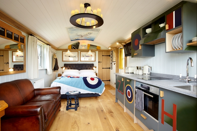 Inside shepherd hut which has a leather sofa and is themed with aeroplane decor