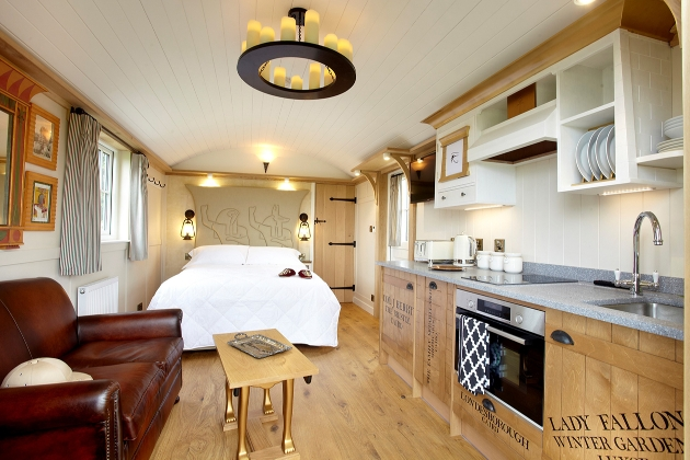 inside shepherd hut which has a leather sofa, wooden kitchenette, and Egyptians inspire decor