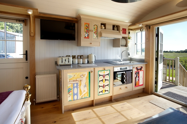 kitchenette inside shepherds hut with drawn images on the cupboard