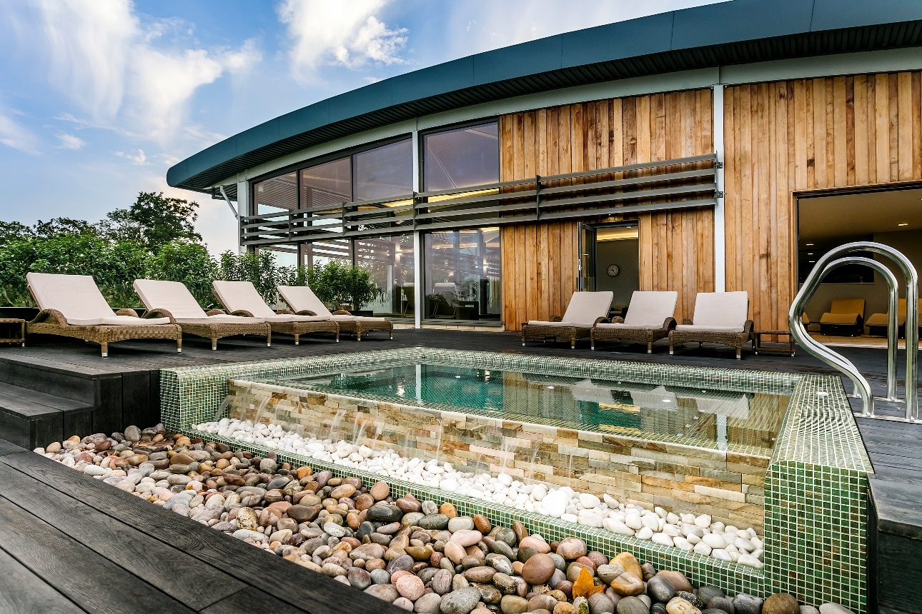 wooden spa building with hot tub with infinity edge on decking with sunloungers