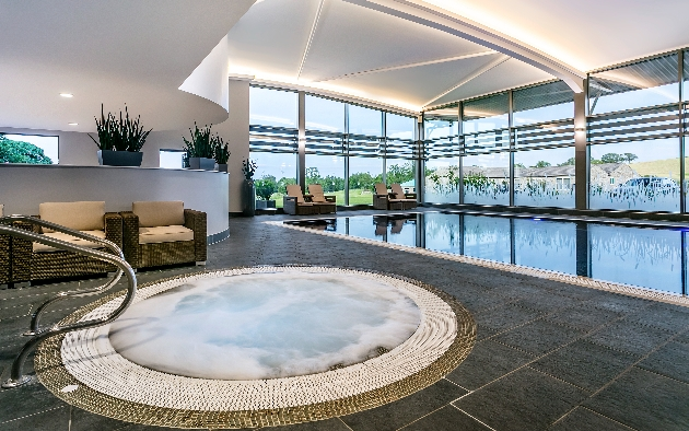 whirlpool jacuzzi in a spa and pool area with panoramic windows