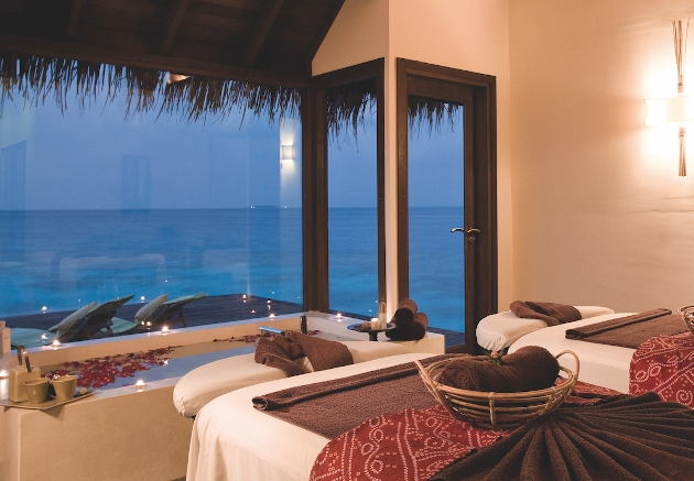 spa beds next to window looking out at ocean