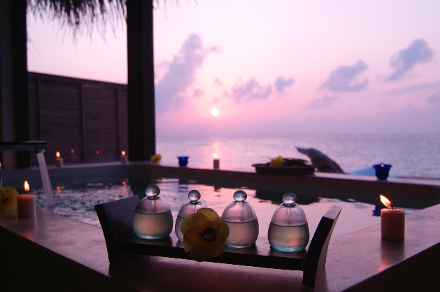 oil bottles next to hot tub at night with ocean view