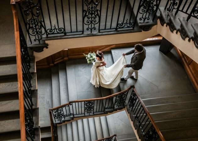 bride walking down stair in her wedding dress train being held by a man